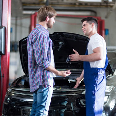 Auto shop mechanic handing keys to customer to his repaired car