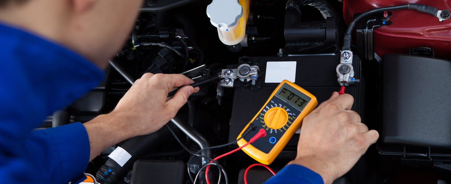 Mechanic testing a car battery