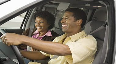Man and Woman smiling while riding in a car