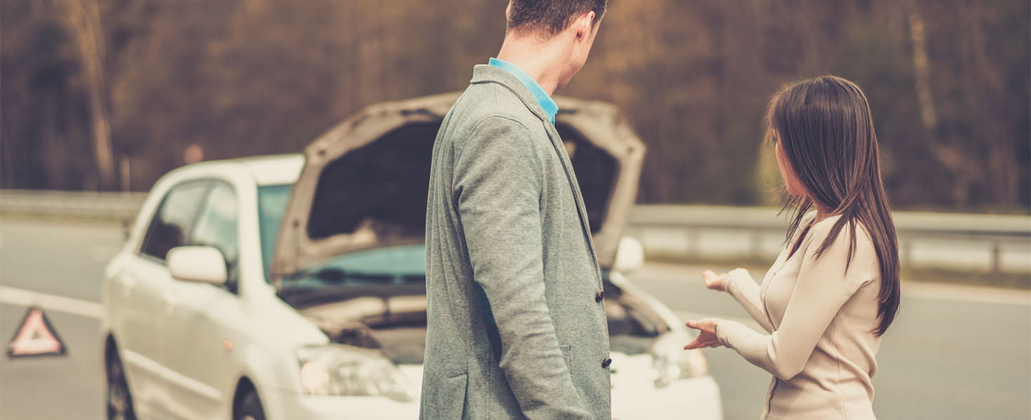 Man and Woman standing in front of broken down car on side of road