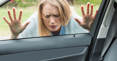 Locked out woman pressed against car window looking at her keys on the seat