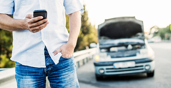 Man standing on side of road holding his phone next to broken down car
