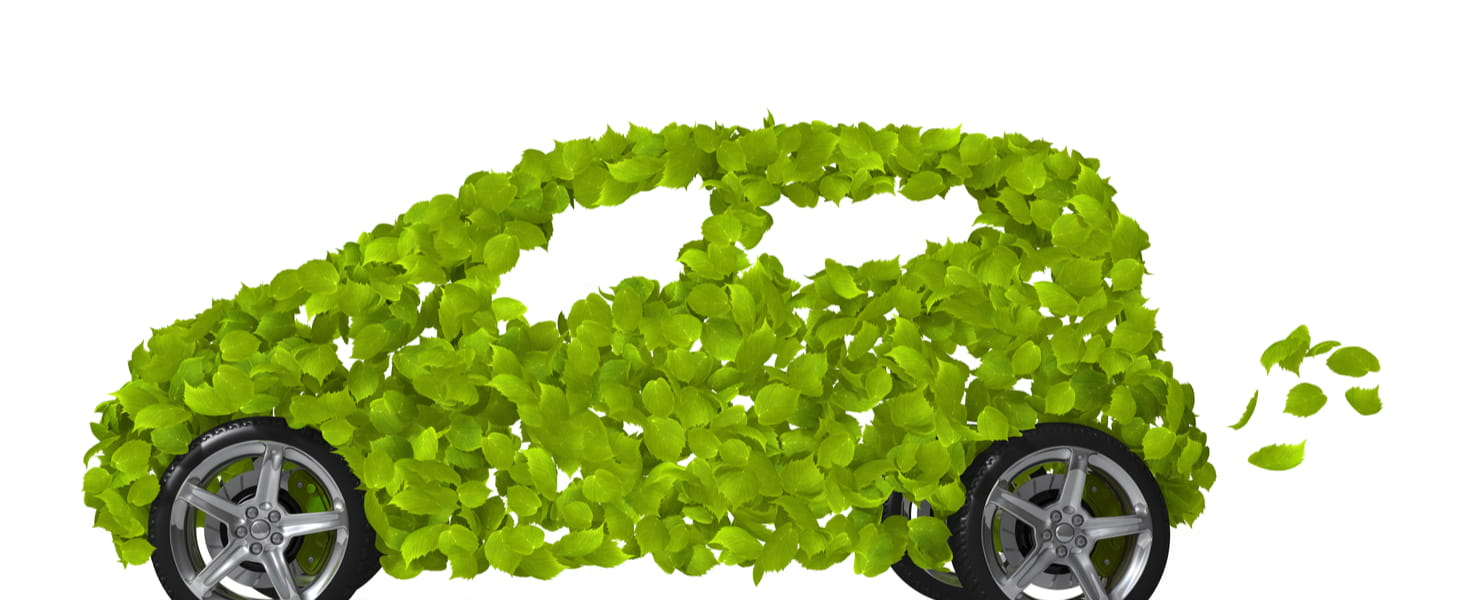 A green car is made up entirely of green leaves set on four tires with fancy chrome wheels.