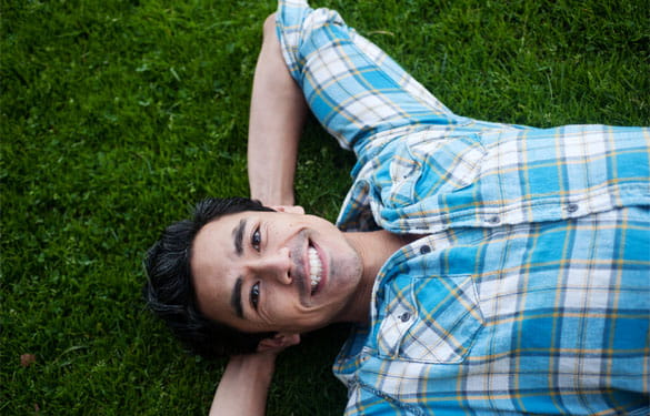Guy smiling while laying in the grass