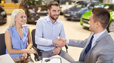 Man and woman finalizing the purchase of a new car