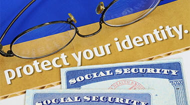 Social security card sitting on a protect your identity sign