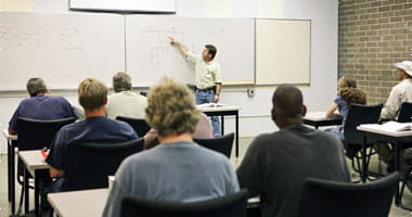 Adult teacher pointing to a diagram on the board in a classroom