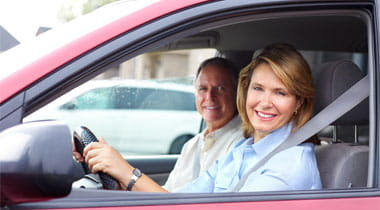 Elderly couple smiling inside of a car
