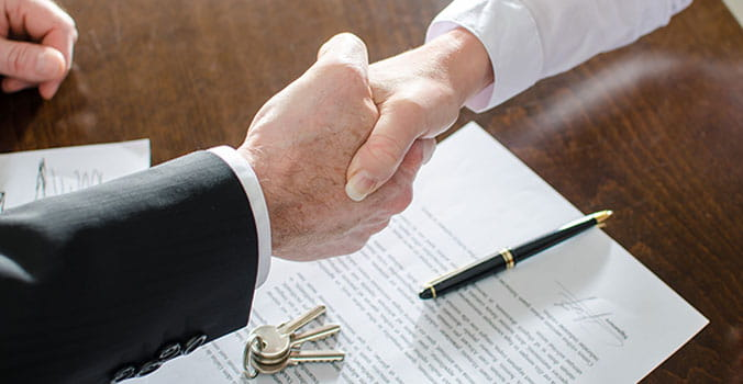 Two men shake hands after signing a contract