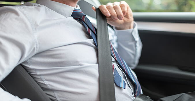 Man putting seat belt on in a car