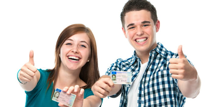 Two teens holding driver's licenses giving the thumbs up
