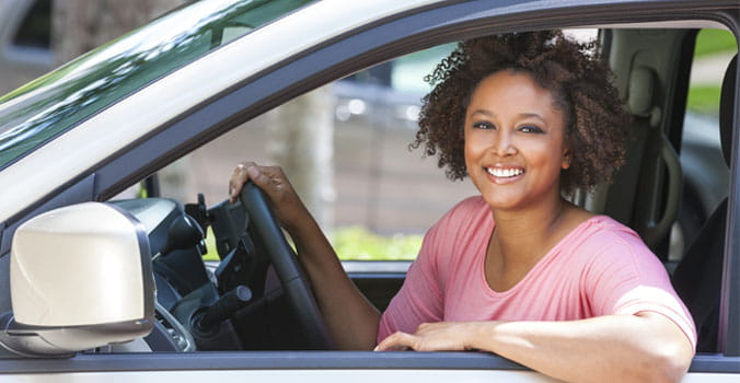 Woman sitting in driver's seat of car smiling