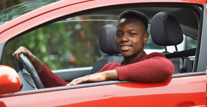 Teen boy sitting in driver's seat of car smiling