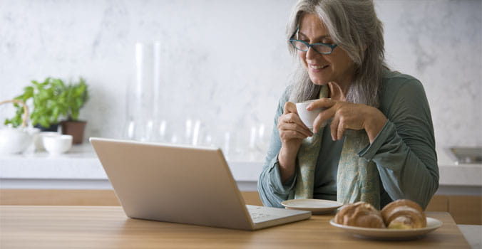 Older woman holding coffee mug reading something on a laptop