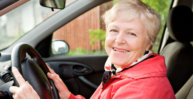Older woman sitting in drivers seat with hands on wheel