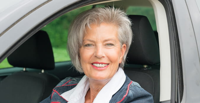 Older woman sitting in driver's seat of car smiling
