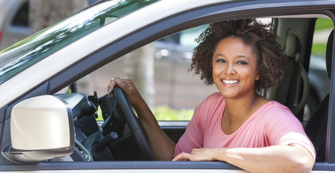 Woman sitting in car with arm rested on open window