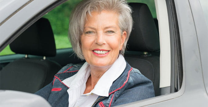 Older woman in drivers seat of car with window down