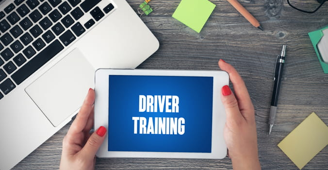 "Woman's hands holding a tablet that reads ""driver training"""