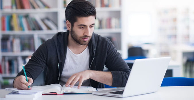 man taking notes sitting in front of a laptop