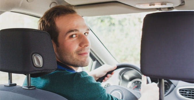 Young man sitting in driver's seat looking behind him