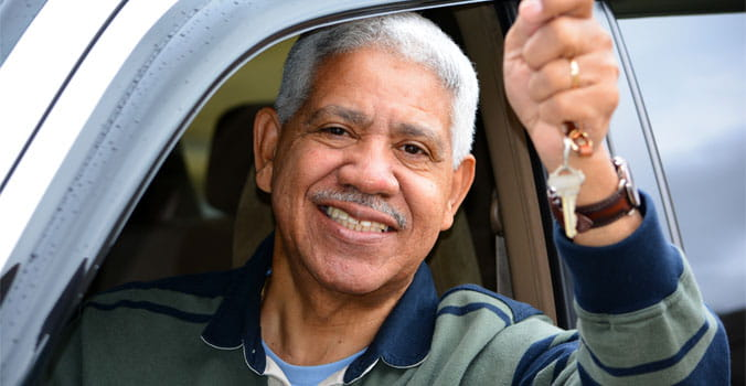 Older man sitting in driver's seat with keys in hand out the window