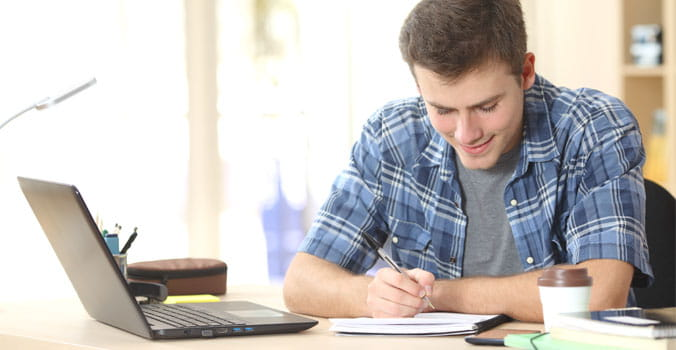 Young man writing in front of a laptop