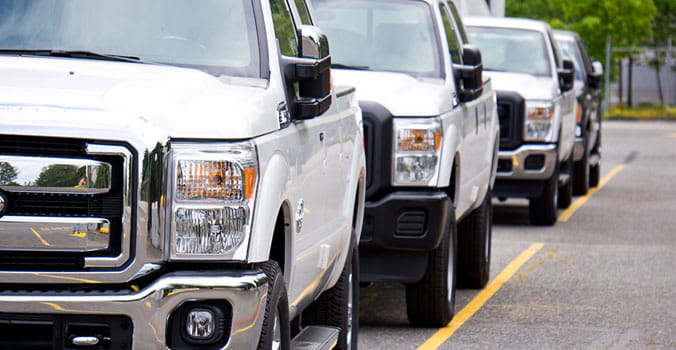 front side view of white trucks lined up in a row