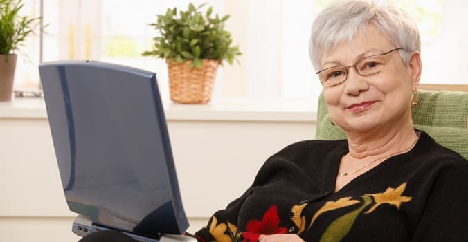 Older woman sitting at home with a laptop in her lap