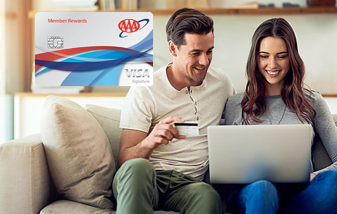Couple looking at laptop with image of Member Rewards Visa card
