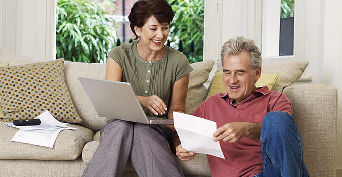 older couple reviewing bills and smiling