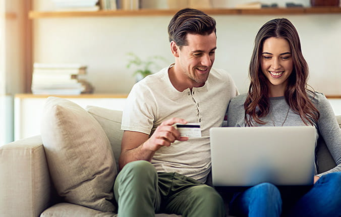 happy couple shopping online with a AAA Member Rewards Visa card