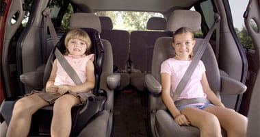Two young girls seating in the back of a van