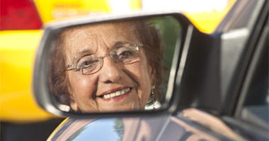 Senior Citizen Smiling with her face in the side mirror