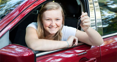 Blond teenage girl sitting in her new car, holding the keys
