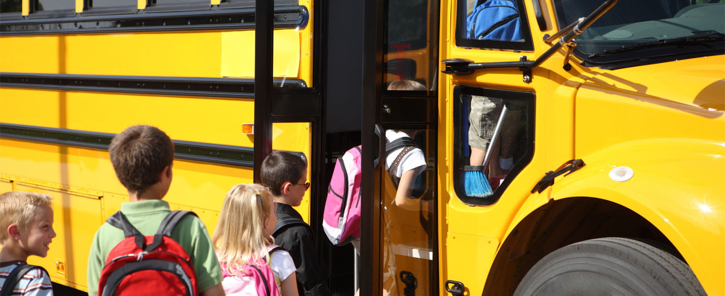 Elementary School Students Getting On Yellow School Bus