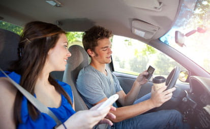 Teens Driver and Friend Distracted by Looking at Cellphones on The Road