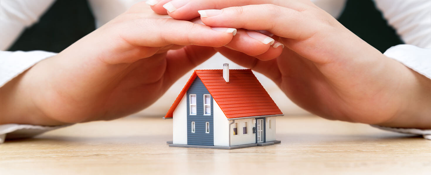 Toy model house covered by women hands