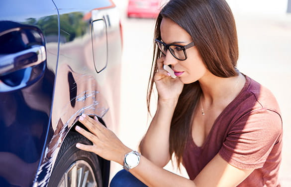 woman looking at a bad scratch to her car
