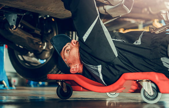mechanic under a car doing a repair