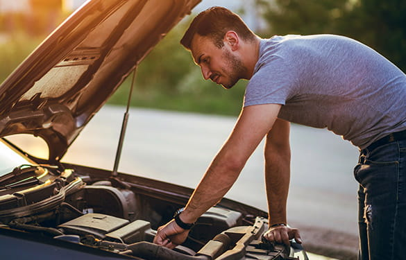 Man looking at the engine of a car looking for a weird smell