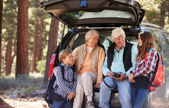 grandparents and kids sitting in the back of a sport utility vehicle