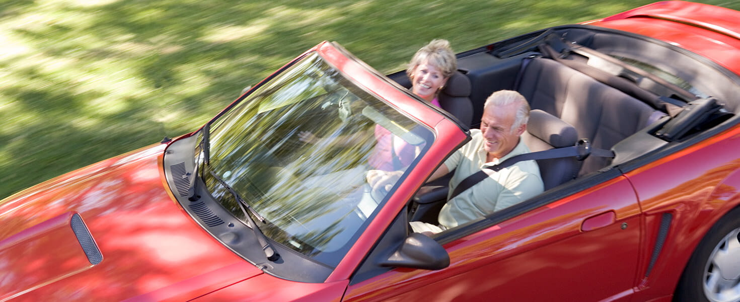 senior couple driving in a fun red convertible