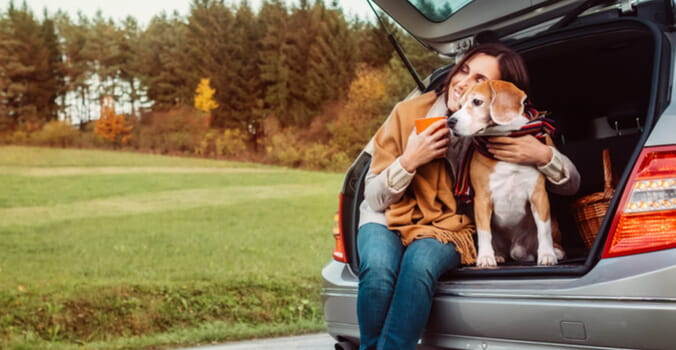 woman with her dog in the back of a car