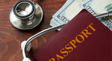Stethoscope, passport and money laying on a table