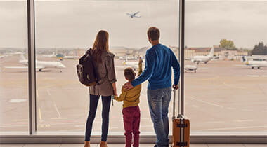 Family of three looking out the airport window