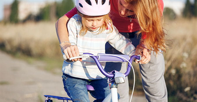 Mother teaching daughter how to ride a bike