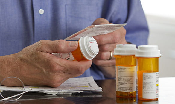 Man Reading Prescription Medication on Pill Bottles