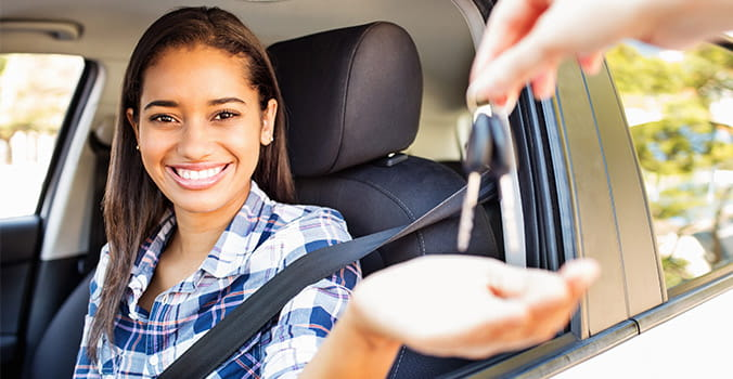 woman happy to get the keys of the new car she purchased