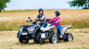 Couple driving off-road with quad bike or ATV